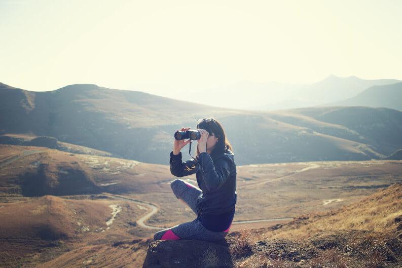 Hochsensibel auf Jobsuche - Frau mit Fernglas in Hügellandschaft