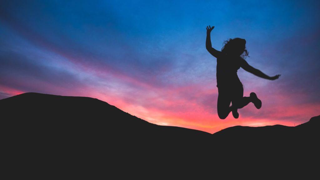Springende Frau vor farbigem Himmel - Hochsensibilitaet berufliche Krise Erfolg